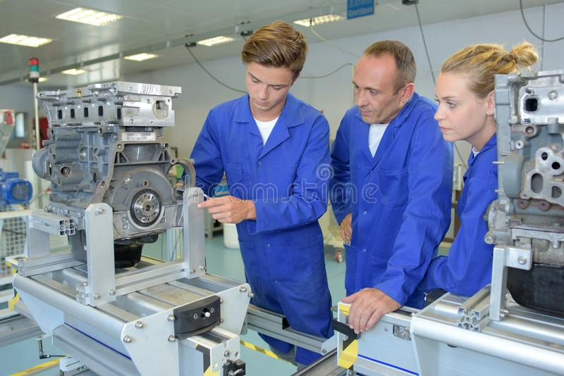 Apprentice setting up machinery royalty free stock photography