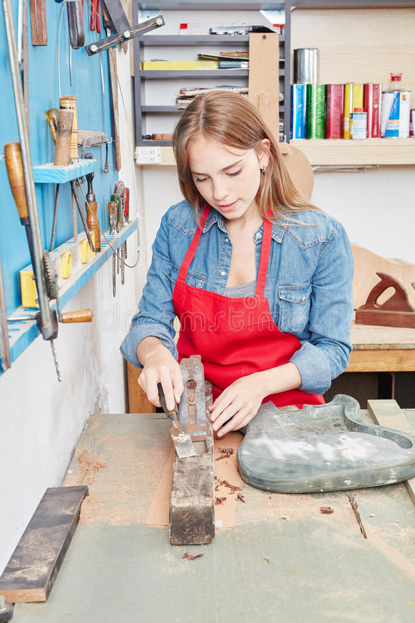 Apprentice woman working with chisel. In carpenter`s shop stock image