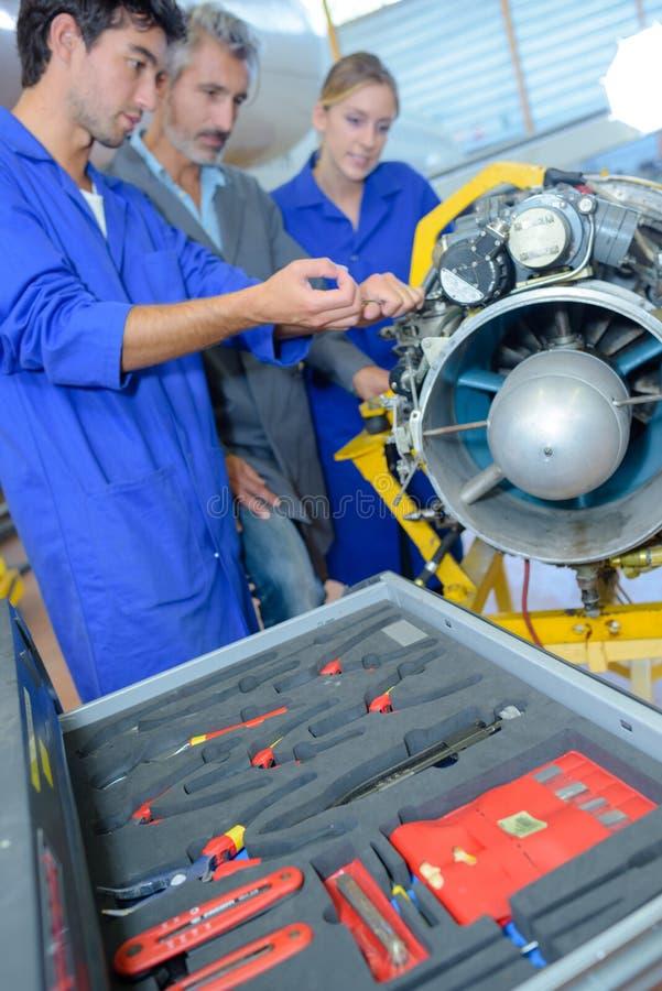 Apprentices авиационные инженеры уча с их профессором стоковое изображение rf