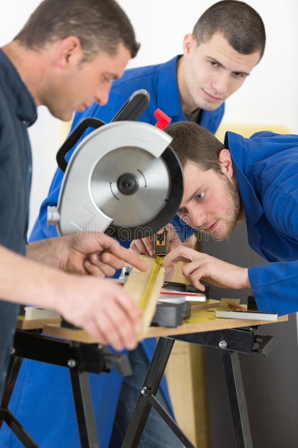 Apprentices learning to use circular saw. Apprentice royalty free stock photo