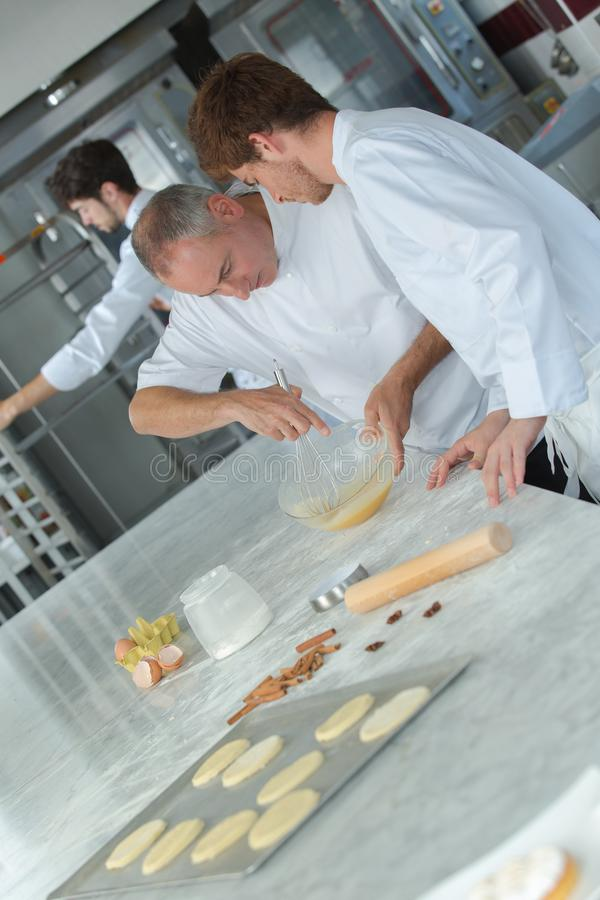 Apprentices in pastry learning with experienced chef. Apprentices royalty free stock photos