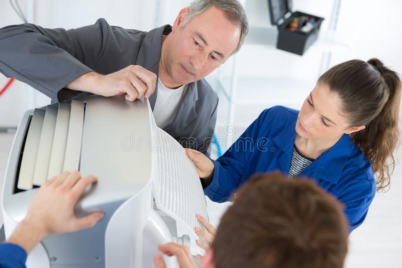 Apprentices and technician inspecting aircondition. The apprentices and technician inspecting aircondition royalty free stock photo