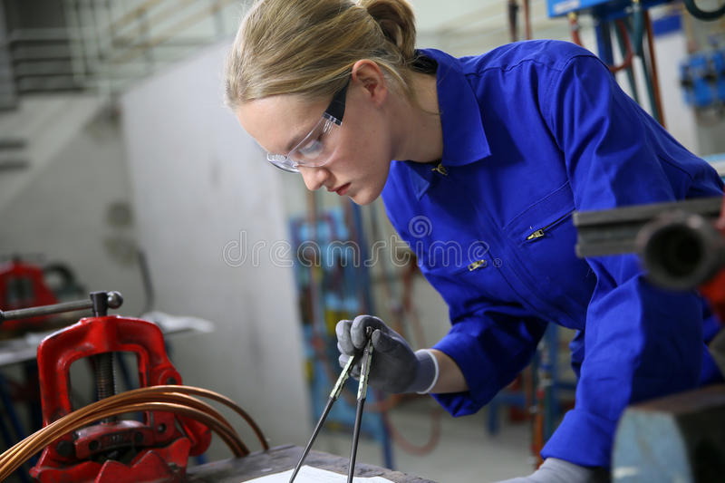 Apprentie de jeune femme dans le plumbery photographie stock