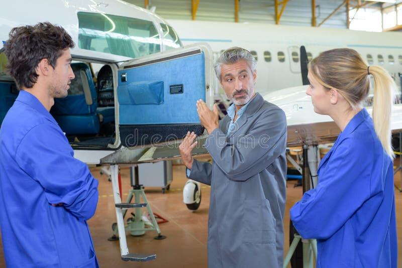 Apprentis de l'avionique dans le hangar image stock