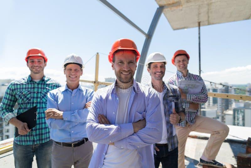 Apprentis de Team Leader Over Group Of de constructeurs au chantier de construction, concept de sourire heureux de travail d'équi photos stock