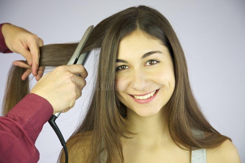 Apprettatrice professionale dei capelli che riveste di ferro capelli lunghi della donna sorridente sveglia immagine stock