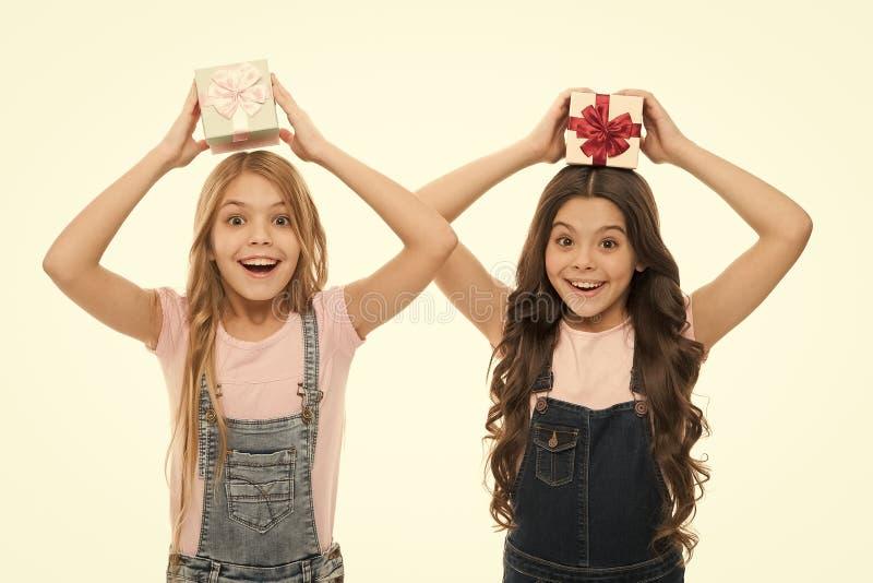 Appris à faire un emballage cadeau Joyeuses petites filles tenant des boîtes-cadeaux au-dessus de la tête Petits enfants avec des photos libres de droits