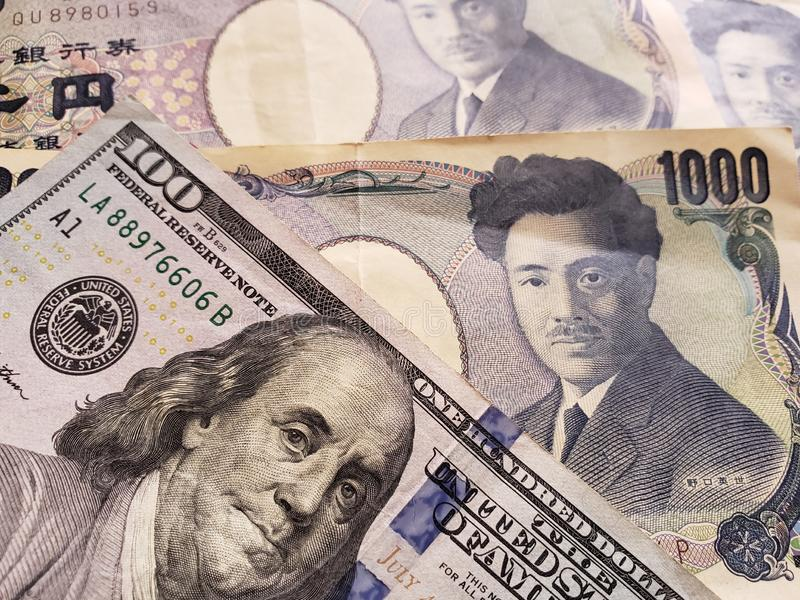 approach to American banknote of 100 dollars and Japanese banknotes of 1000 yen royalty free stock photos