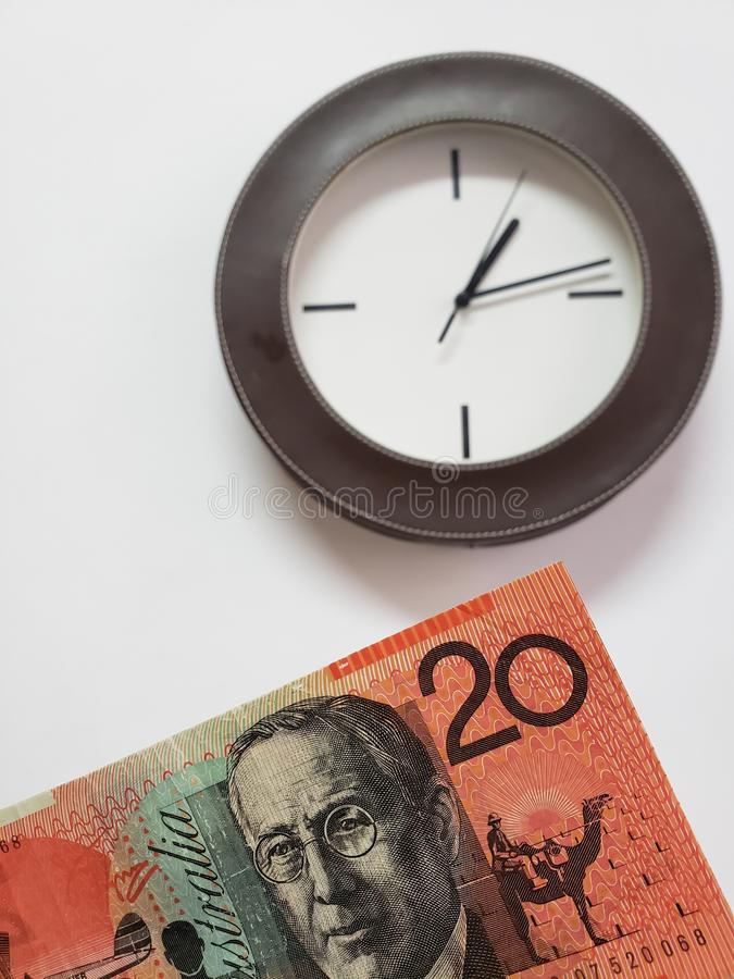 Approach to Australian banknote of twenty dollars and background with a circular wall clock. Clock, time, space, moment, schedule, agenda, hour, minute, second stock photo