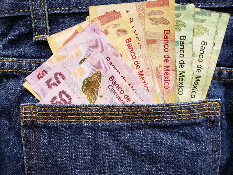 approach to back pocket of jeans in blue with Mexican banknotes royalty free stock photography