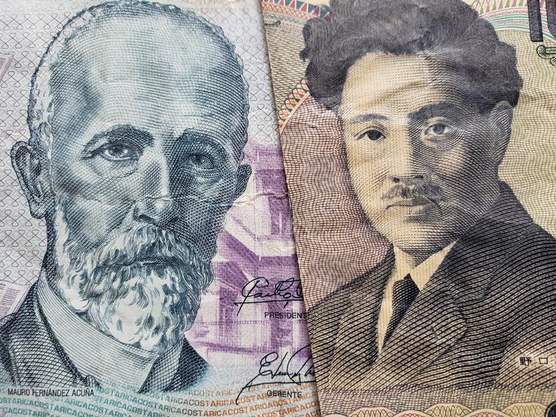 approach to Costa Rican banknote of 2000 colones and Japanese banknote of 1000 yen stock photo