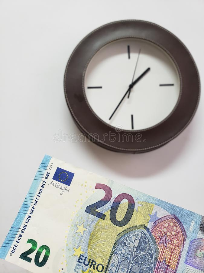Approach to European banknote of twenty euro and background with a circular wall clock stock photo