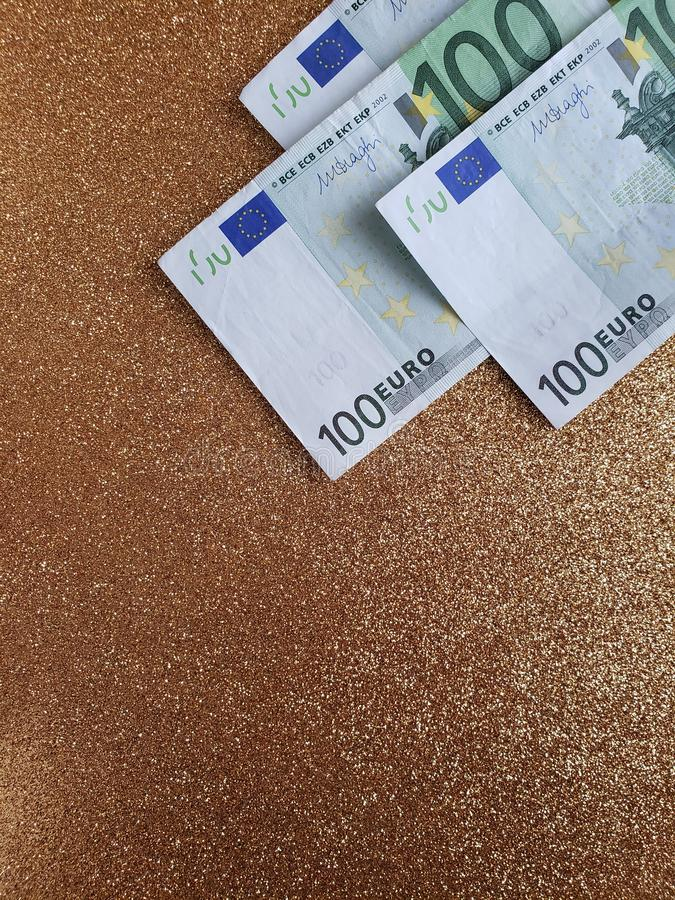 Approach to european banknotes of 100 euro and background in metallic gold color. Golden, offer, promotion, backdrop, colorful, texture, bright, commerce royalty free stock photography