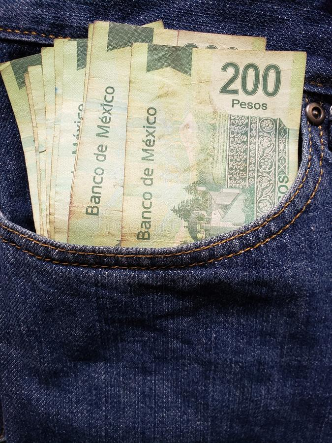 approach to front pocket of jeans in blue with Mexican banknotes royalty free stock images