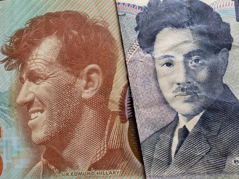 Approach to New Zealand banknote of five dollars and Japanese banknote of 1000 yen. Commerce, exchange, trade, trading, value, buy, sell, profit, price, rate royalty free stock image