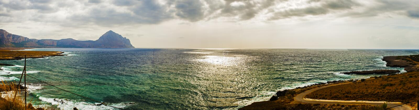 Approaching storm on a beach of Sicily. The sun filters through a hole in the clouds and stormy royalty free stock images