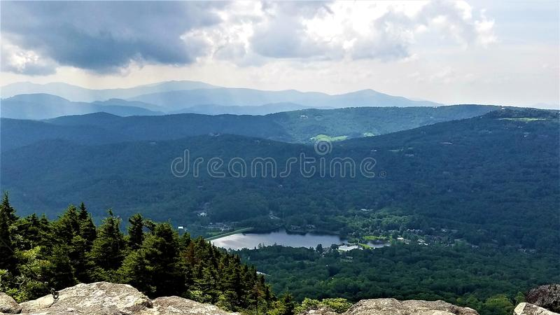 Approaching storm over Grandfather Lake. Sun rays try to break through threatening rain clouds over Grandfather Lake at the base of Grandfather Mountain near royalty free stock image