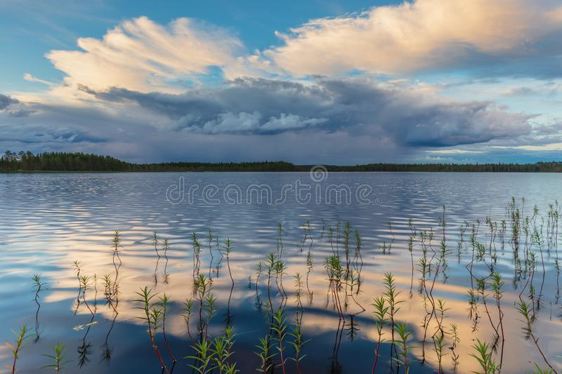 Approaching thunder cloud over a small lake stock image