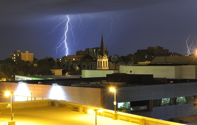 Approaching thunderstorm. Lighting bolts of approaching thunderstorm in the city. Storm approaching at night. Church steeple and parking ramp well light up in stock photography
