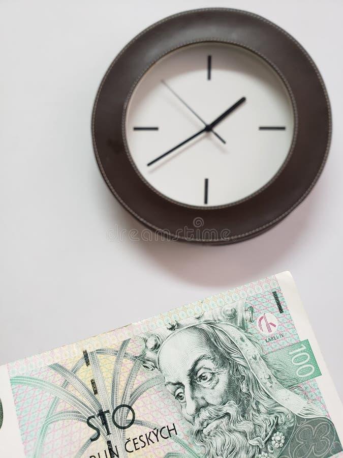 approccio ad una banconota ceca di korun 100 e di fondo con un orologio di parete circolare fotografia stock