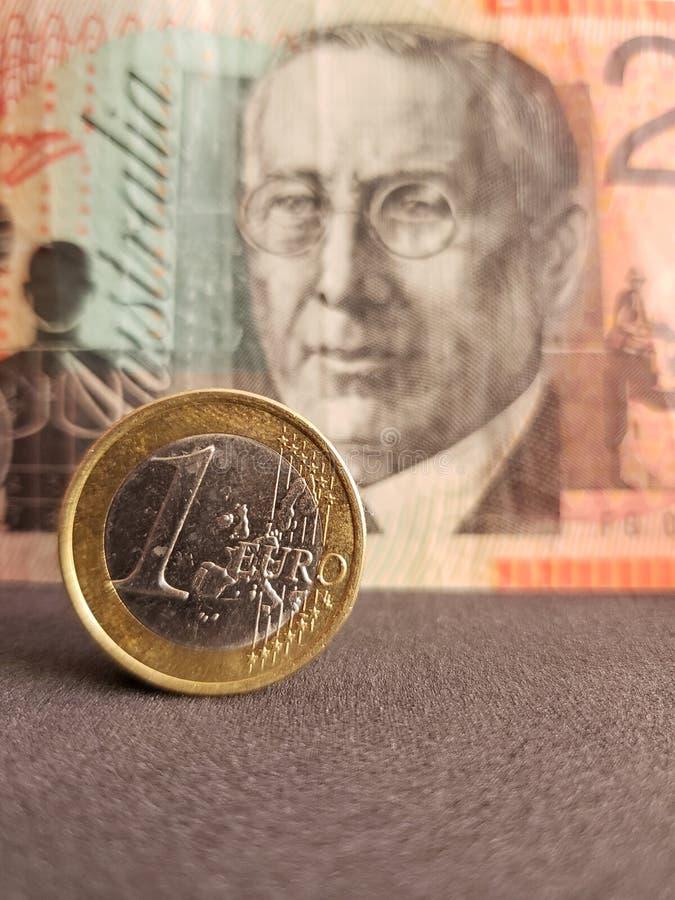 approccio ad una moneta europea di un euro e fondo con una banconota australiana di venti dollari fotografia stock libera da diritti