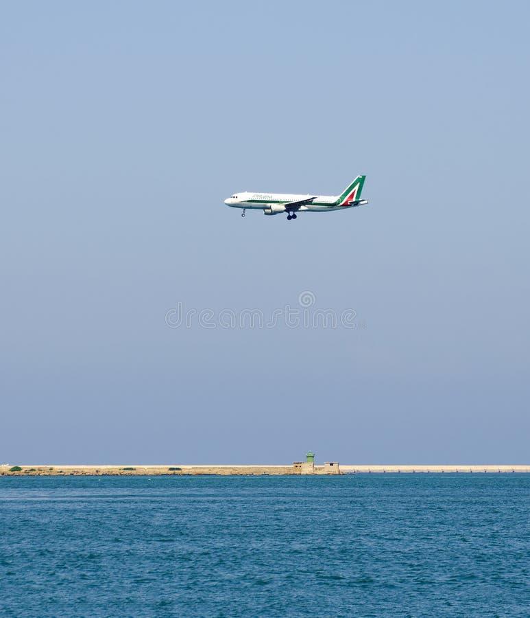 Approccio di atterraggio di un aeroplano sopra acqua fotografia stock