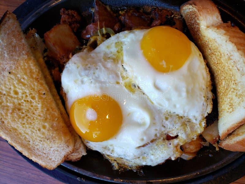 approche à un plat avec des oeufs au plat pour le petit déjeuner, le fond et la texture photographie stock libre de droits