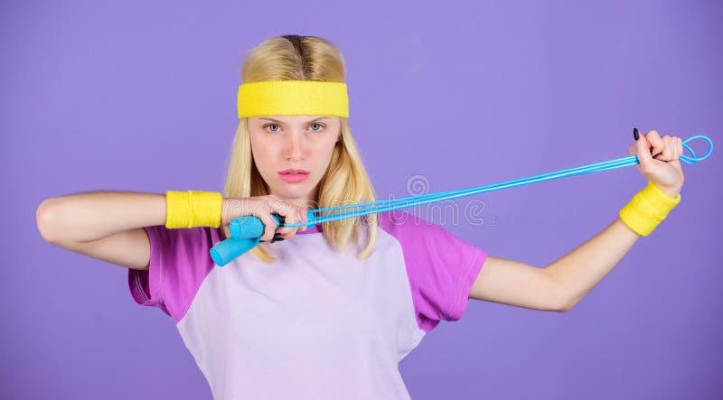 Approche appropriée pour perdre le poids La corde à sauter de prise de fille portent des bracelets lumineux Femme s'exerçant avec photographie stock