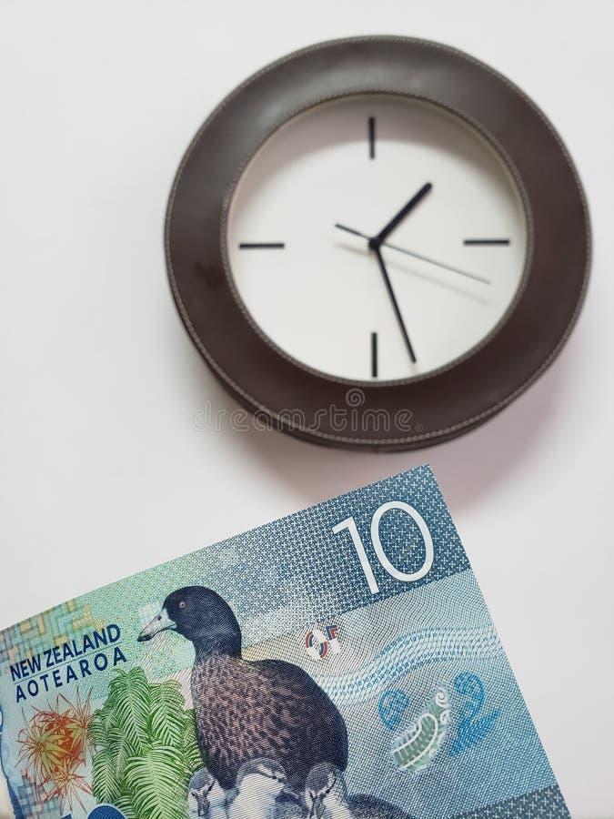 approche au billet de banque du Nouvelle-Zélande de dix dollars et fonds avec une horloge murale circulaire images stock