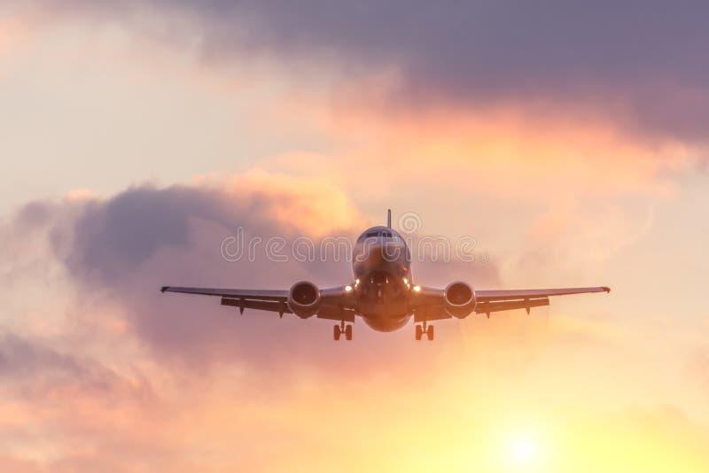 Approche de vol d'avion de passager dans les nuages au coucher du soleil image stock