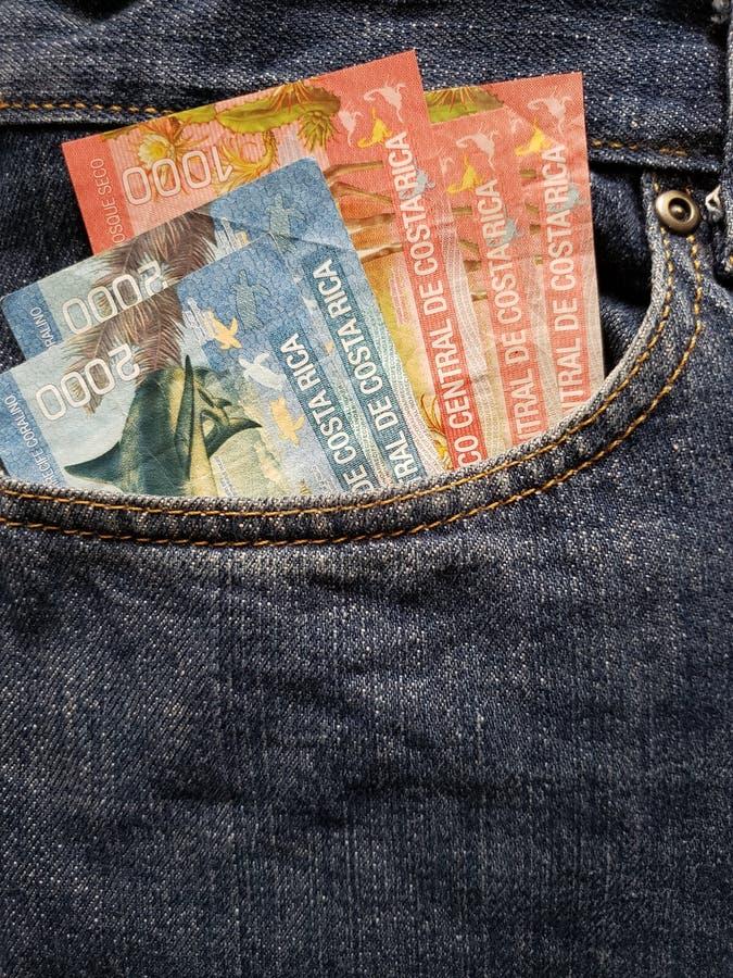 approche pour affronter la poche de jeans dans le bleu avec des billets de banque de Costa Rican images stock