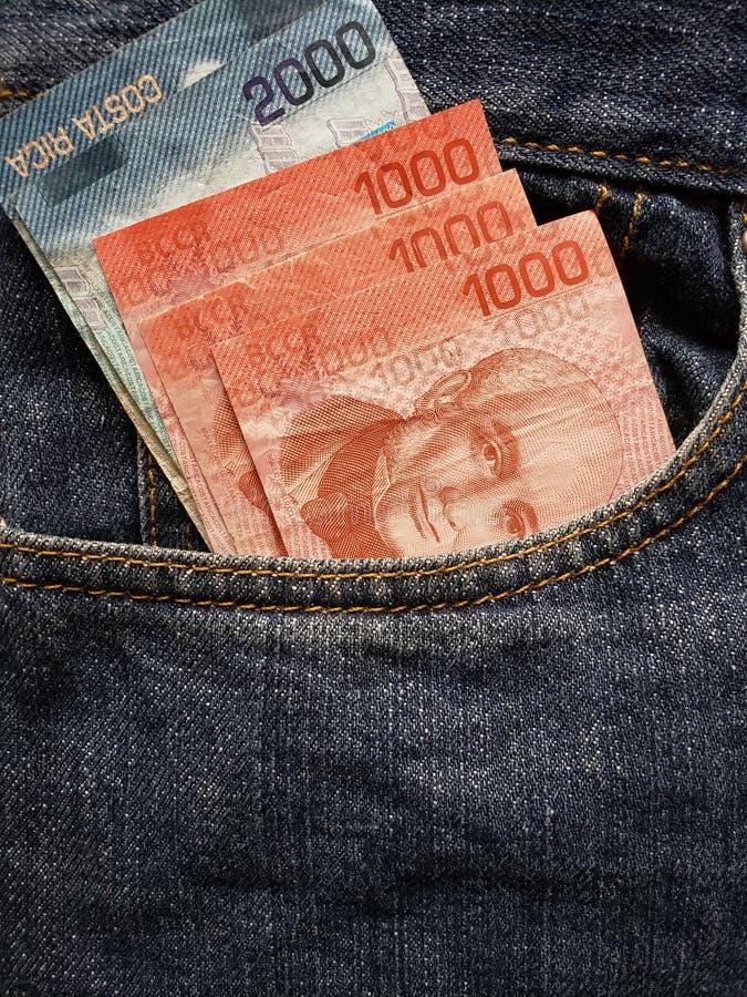 approche pour affronter la poche de jeans dans le bleu avec des billets de banque de Costa Rican image libre de droits