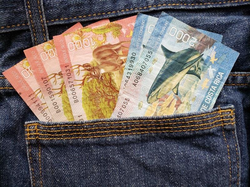 approche pour soutenir la poche de jeans dans le bleu avec des billets de banque de Costa Rican photographie stock