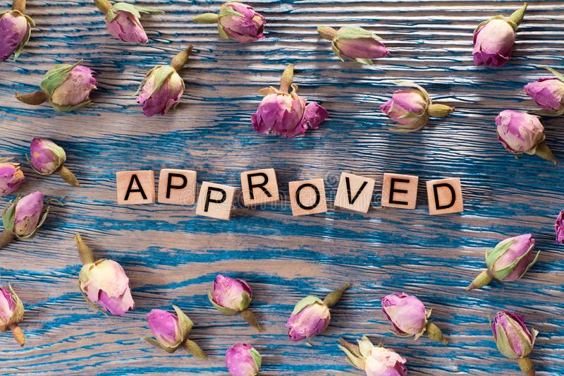 Approved on wooden cube. The words approved write on wooden cubes with rose bud on blue color wood background royalty free stock image