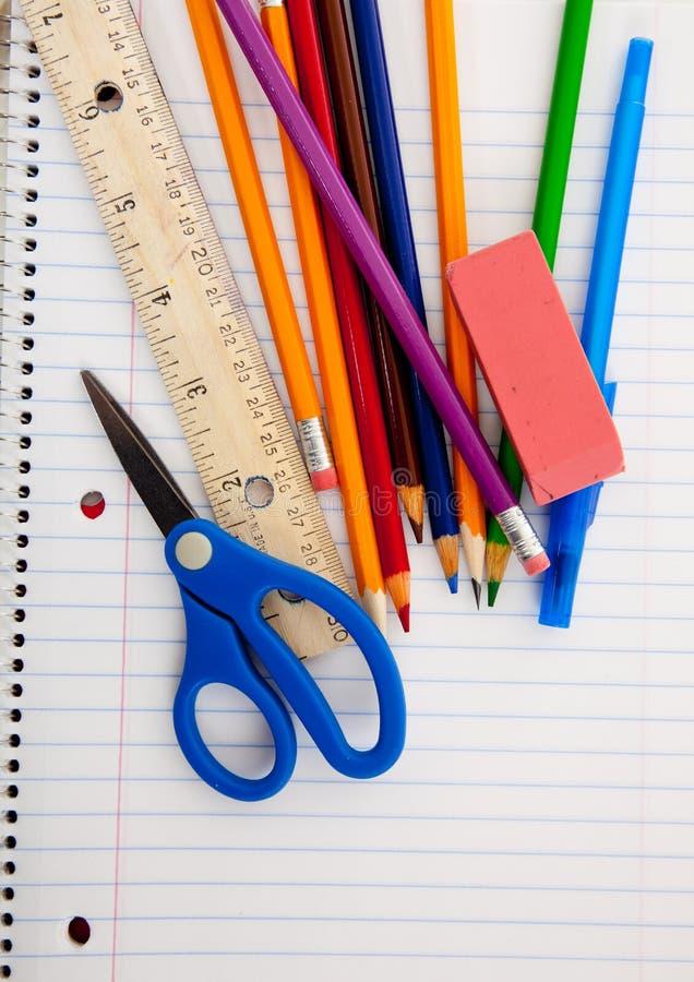 Approvisionnements d'école assortis sur un cahier rayé photographie stock libre de droits