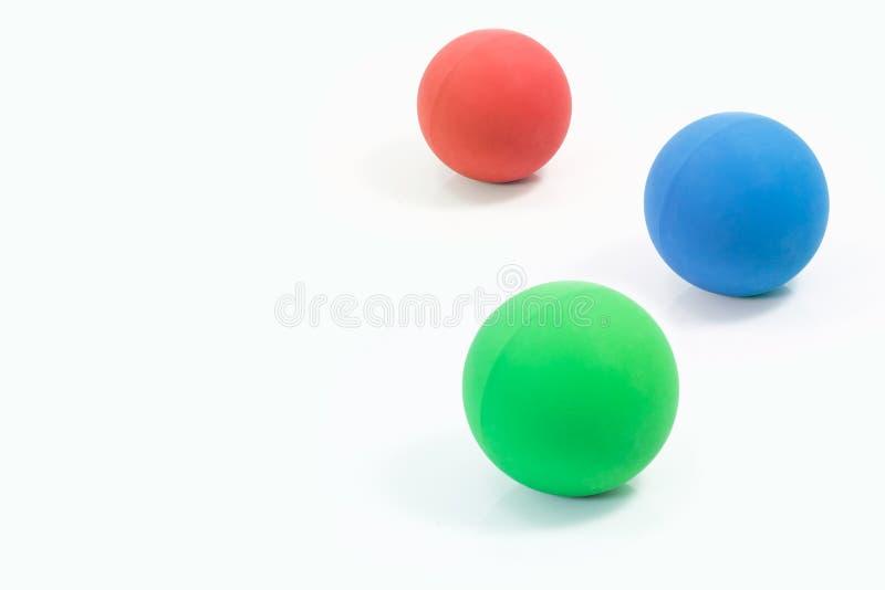 Approvisionnements d'animal familier au sujet des boules en caoutchouc du rouge, du vert et du bleu pour l'animal familier o photo libre de droits
