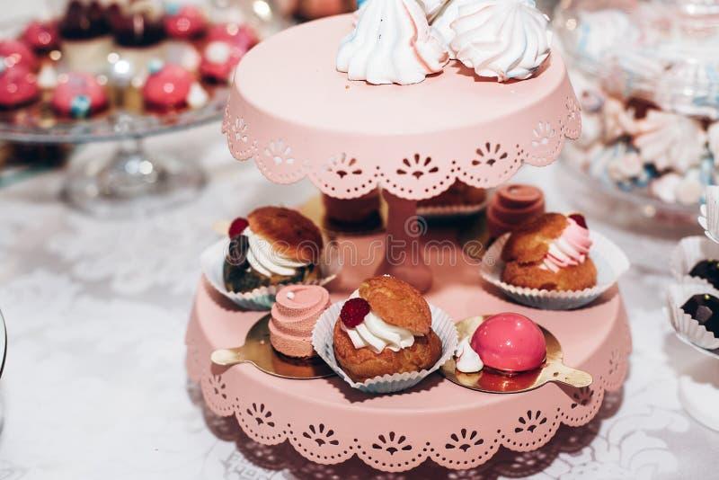 Approvvigionamento di lusso di nozze, tavola rosa con i dessert moderni, cupcak fotografie stock libere da diritti