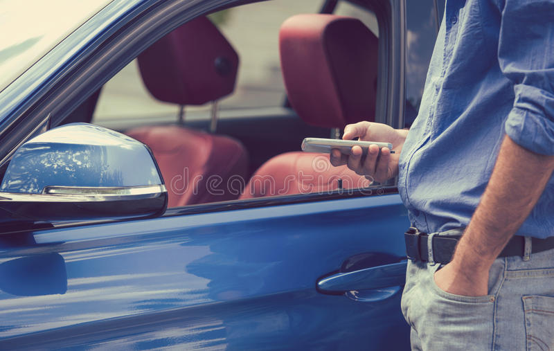 Apps del teléfono móvil para los dueños de vehículo Hombre que usa el teléfono elegante para controlar su coche foto de archivo