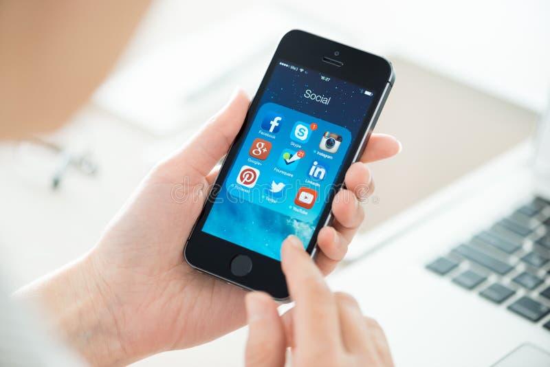 Apps sociales del establecimiento de una red en el iPhone 5S de Apple imágenes de archivo libres de regalías