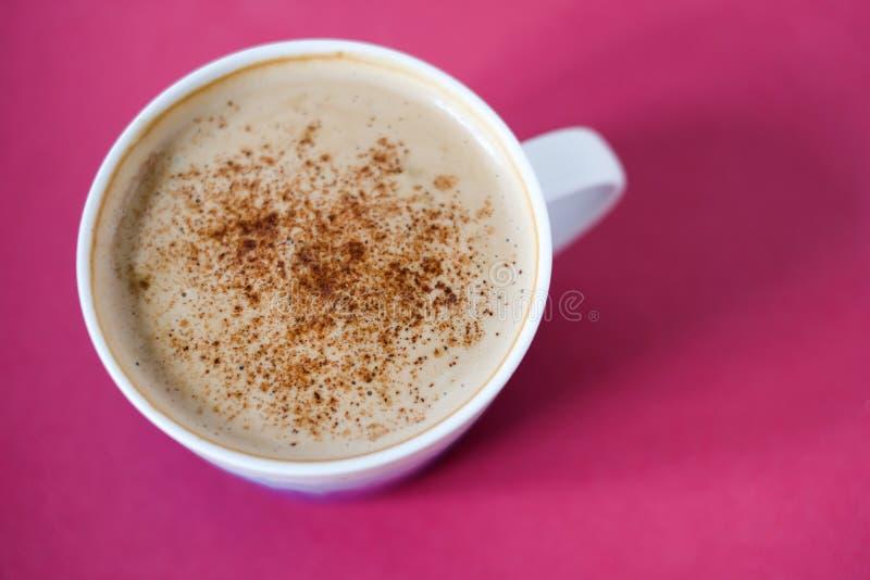 Appuccino πρωινού Φλιτζάνι του καφέ με τον αφρό και την κανέλα γάλακτος ή σκόνη κακάου στο φωτεινό ρόδινο υπόβαθρο στοκ φωτογραφία με δικαίωμα ελεύθερης χρήσης