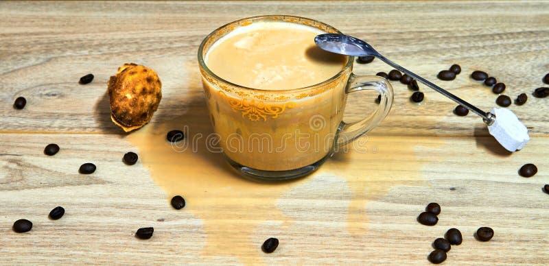 appuccino med korn av kaffe på en trätabell arkivfoto