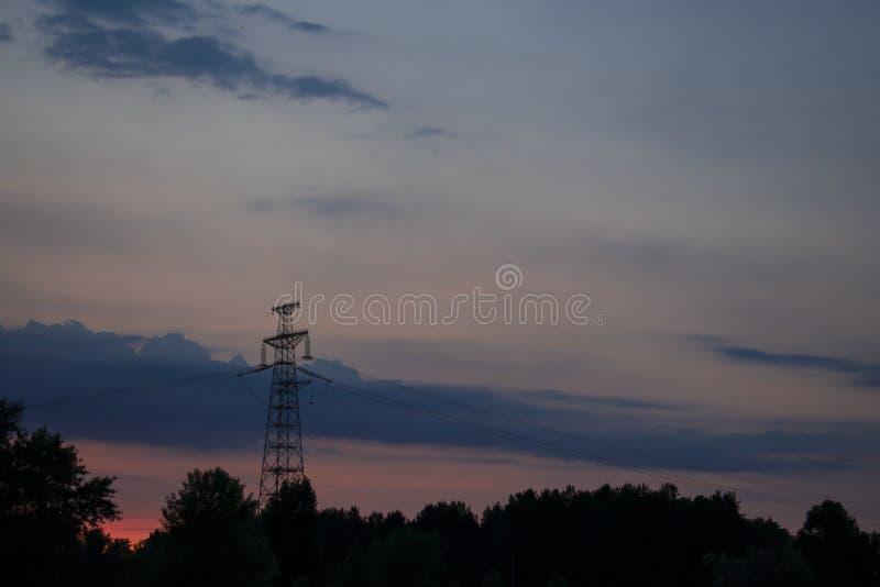 Appui de la ligne de transmission électrique contre le ciel et le su photographie stock