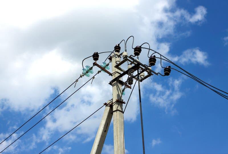 Appui vertical de ligne d'alimentation d'énergie au-dessus de ciel bleu avec les nuages blancs images stock