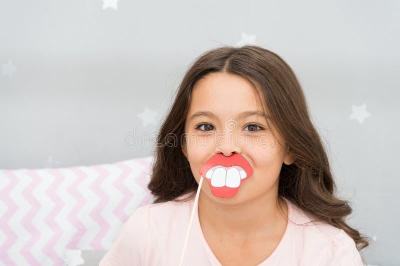 Appui verticaux de cabine de photo de soirée pyjamas La pose gaie de fille d'enfant avec les lèvres toothy de bouche sourient att image stock