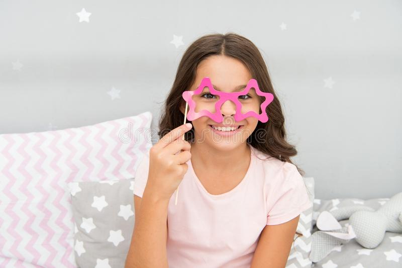Appui verticaux de cabine de photo de soirée pyjamas La pose gaie de fille d'enfant avec les lunettes en forme d'étoile font la f images libres de droits