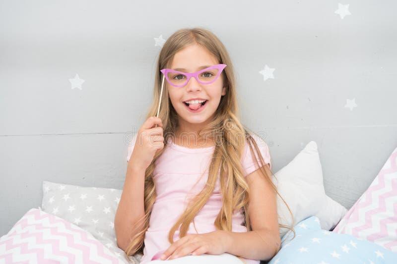 Appui verticaux de cabine de photo de soirée pyjamas La pose gaie de fille d'enfant avec les lunettes roses font la fête l'attrib image libre de droits