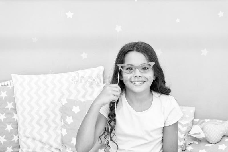 Appui verticaux de cabine de photo de soirée pyjamas La pose gaie de fille d'enfant avec de rétros lunettes roses font la fête l' photo libre de droits