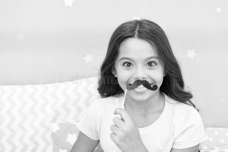 Appui verticaux de cabine de photo de soirée pyjamas Pose gaie de fille d'enfant avec l'attribut noir de partie de moustache Prép photos libres de droits