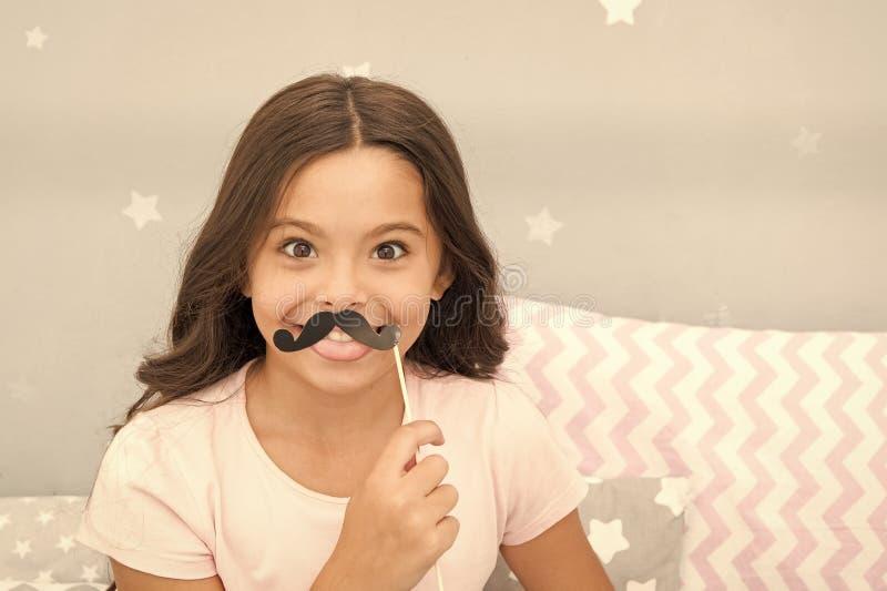 Appui verticaux de cabine de photo de soir?e pyjamas Pose gaie de fille d'enfant avec l'attribut noir de partie de moustache Pr?p photos stock