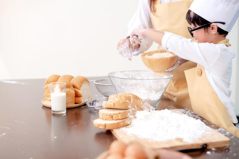Appy Asian kid helping mom for cooking. Preparing an ingredient with powder and flour. stock photo